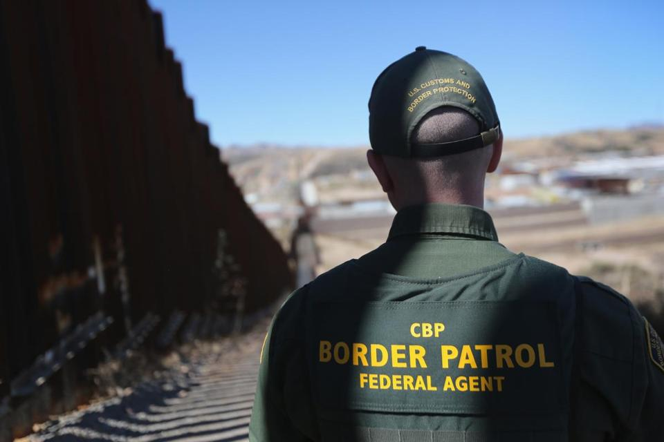 A US Border Patrol agent scanned a section of the recently constructed fence at the US-Mexico border in Nogales, Arizona. The fence in this area ranges from 18 to 32 feet high.