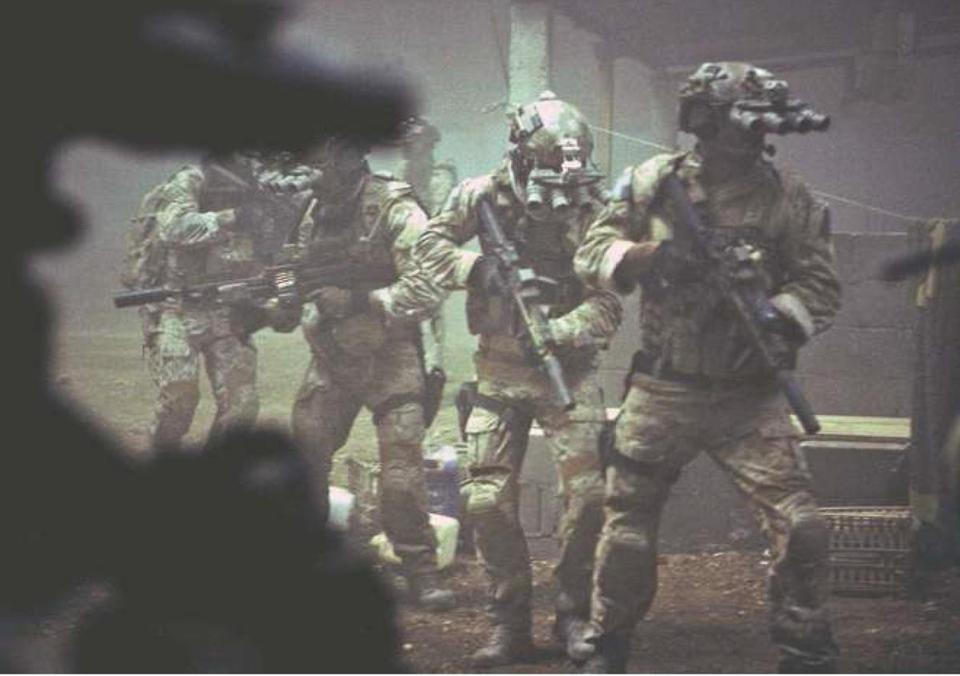 "Navy SEALs are seen through the greenish glow of night vision goggles as they prepare to breach a locked door in Osama bin Laden's compound in a scene from ""Zero Dark Thirty."""