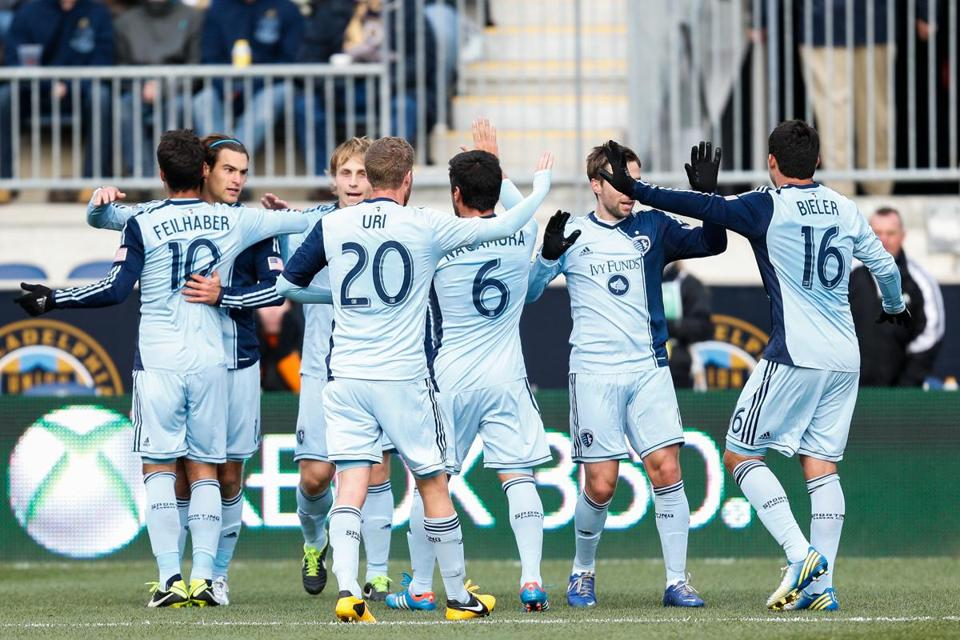 Kansas City's Graham Zusi (facing, left) celebrates after scoring in the first half.