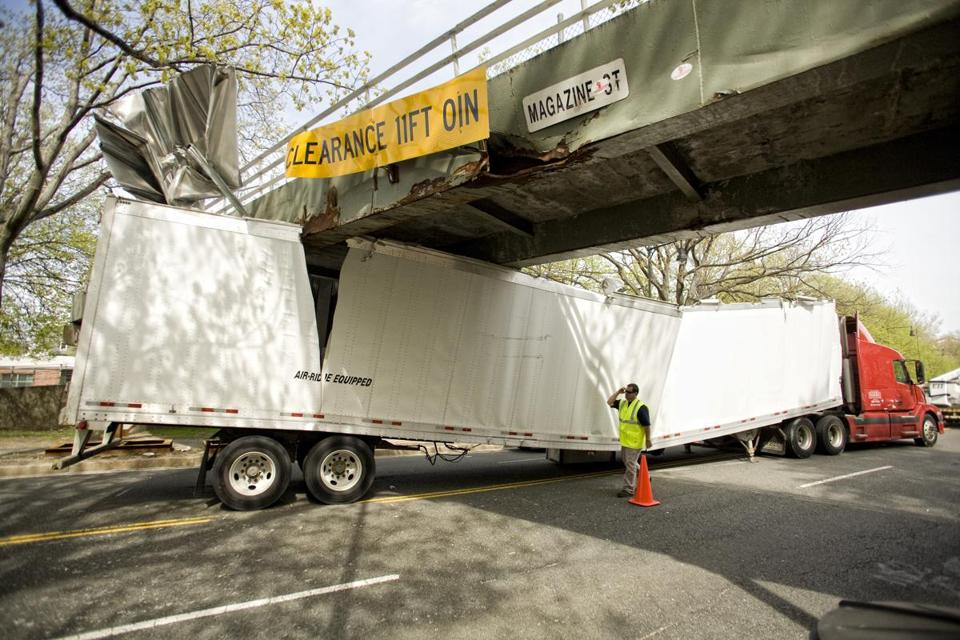 4/30/09 Cambridge, MA -- A tractor trailer on Memorial Drive collided with and became stuck under a pedestrian bridge in Cambridge Thursday afternoon April 30, 2009. According to workers on site the truck was carrying a shipment of computer equipment bound for Micro Center when it missed its turn and collided with the overpass. State Troopers said the driver was carrying paperwork instructing him to disregard signs warning motorists about the bridge's clearance height. Erik Jacobs for the Boston Globe Library Tag 05012009