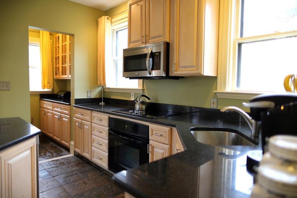 The updated kitchen has dark granite counters, a breakfast island, and a pantry.