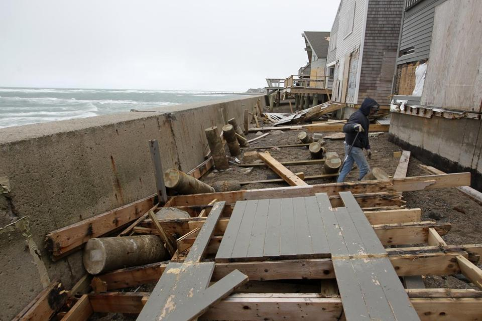 Joe Norton dismantled a deck damaged from a previous storm in Scituate. Coastal residents have been advised to leave as a new storm nears.