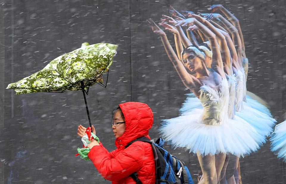Winds pulled a woman's umbrella at Tremont and Stuart streets in Boston Thursday, March 7, 2013.