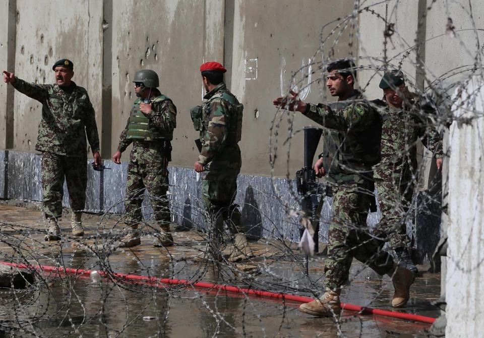 Afghan Army soldiers inspected the scene of a suicide bombing Saturday outside the Defense Ministry in Kabul.