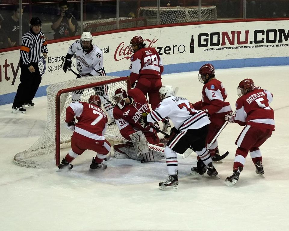 BU goalie Sean Maguire had to check, but he made this save with his pad in a 4-2 victory over Northeastern. The goalmouth scramble was indicative of a wild night in Hockey East; postseason jockeying will come down to the final day on Saturday.