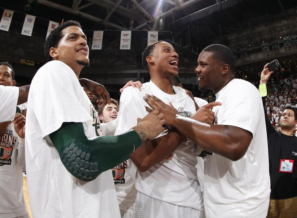 From left, Julian Gamble, Kenny Kadji, and Reggie Johnson celebrate Miami's first outright ACC championship.