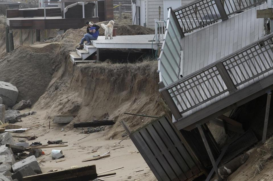 Homeowners on Plum Island embraced on their back porch on Monday amid the wreckage caused by the nor'easter last week. The storm further eroded the island's fragile dunes.