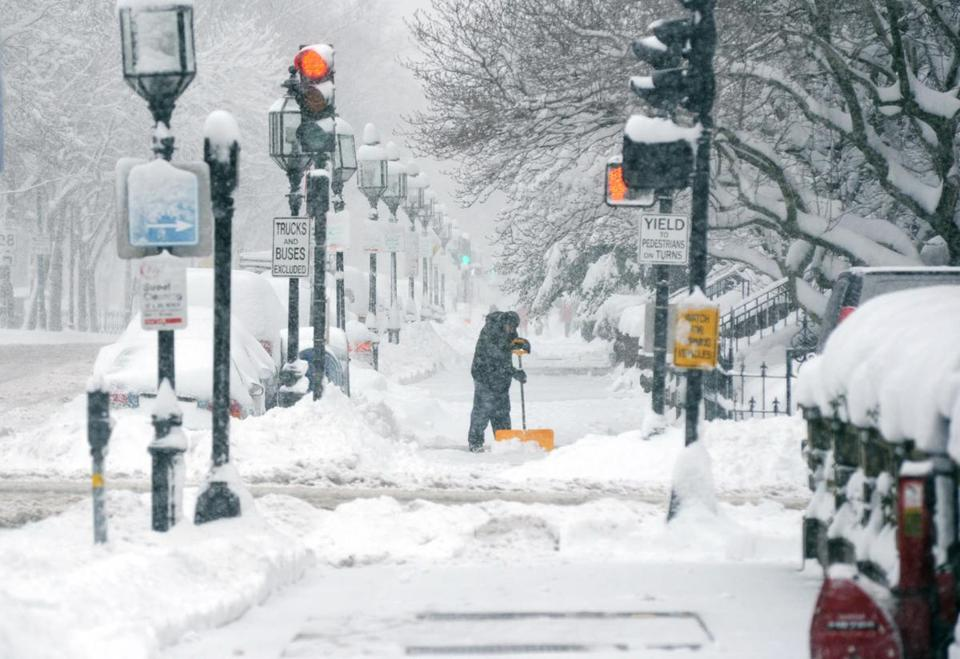 A man shoveled snow on Commonwealth Avenue on Friday.