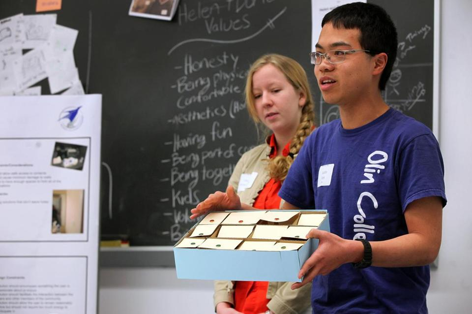 Olin students Justin Poh, right, and Lauren Froschauer, show a model of a possible solution for an assistive device to help a senior citizen remember to take her medications.