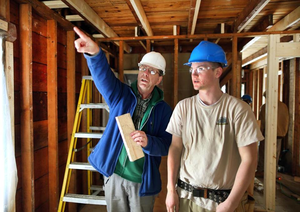 Blue Hills Regional teacher Richard McDonough (left) guides students converting a century-old home into a new town arts center in Braintree.