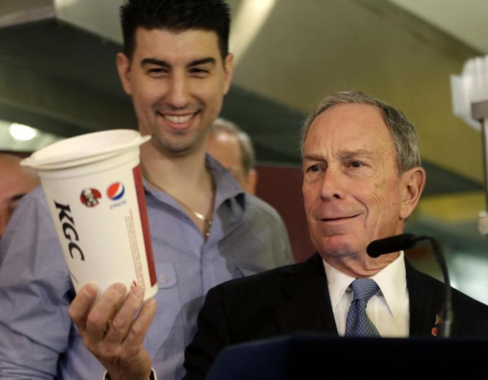 New York City Mayor Michael Bloomberg looked at a 64-ounce cup, as a cafe owner stood behind him.
