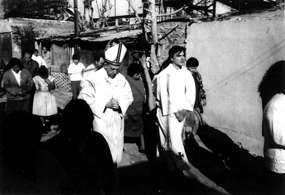 Cardinal Jorge Mario Bergoglio (left) visited a shantytown in Buenos Aires in an undated picture.