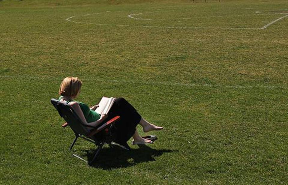 Emily Anthony took her lunch break on a lawn chair with a book at Cold Spring Park in Newton.