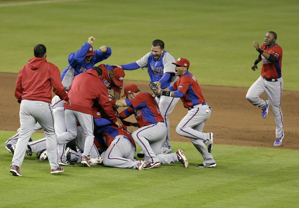 After earning a spot in the final four, Puerto Rico players form a victory pile on the infield.