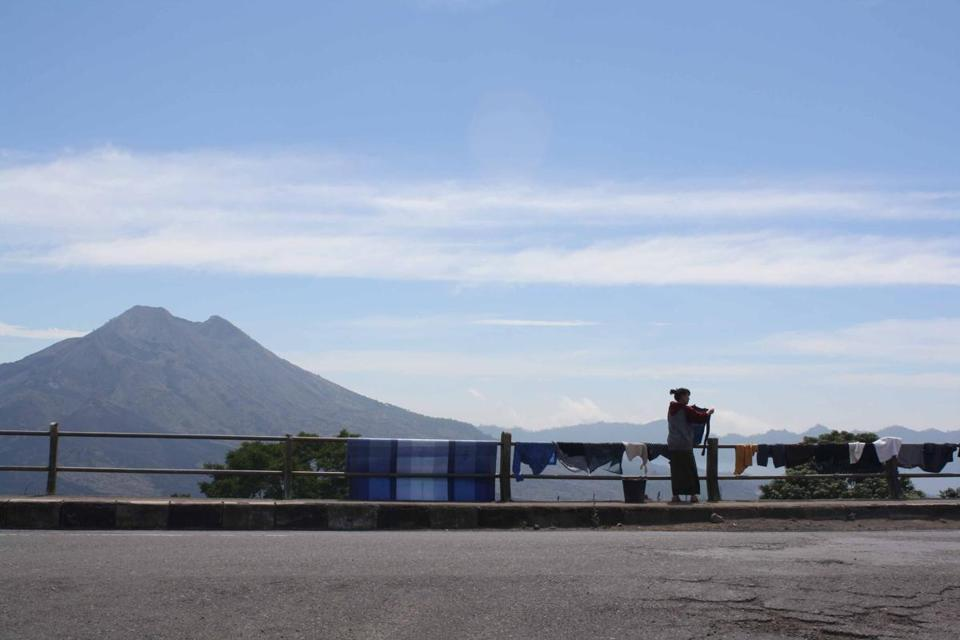 A woman dries clothes along the road to Mount Batur. The volcano is in the background.