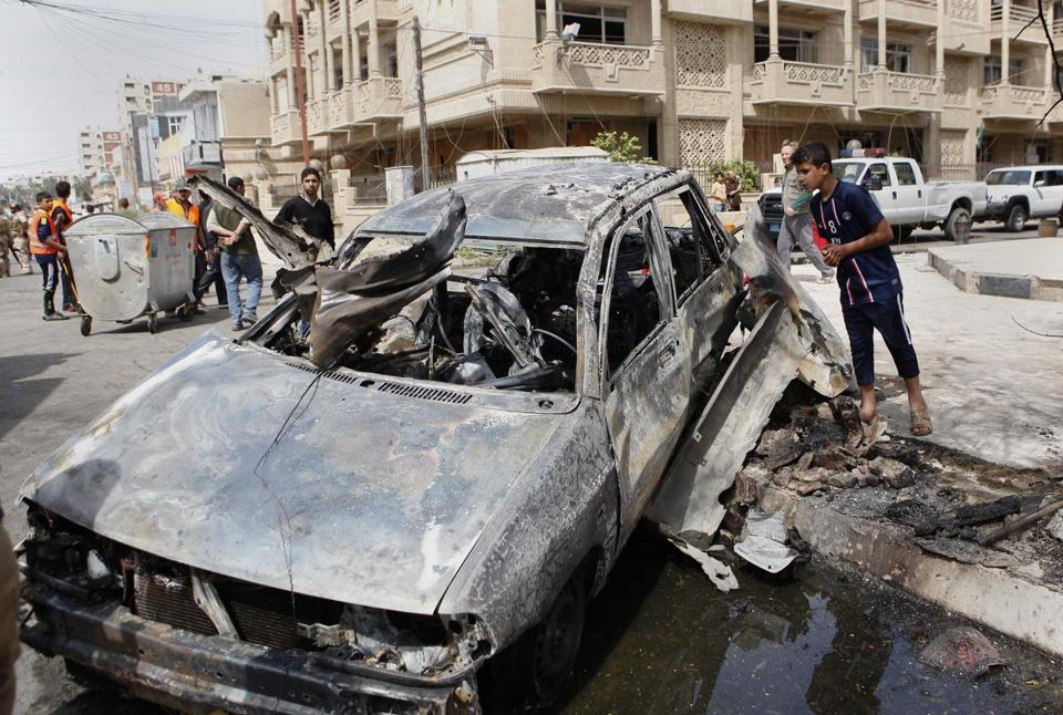 People inspected a car destroyed in a car bomb attack close to one of the main gates to the heavily-fortified Green Zone in Baghdad, Iraq.