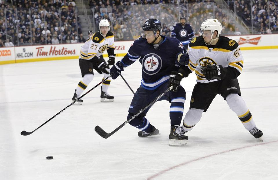Bruins rookie Ryan Spooner (right) and the Jets' Alexander Burmistrov battle for the puck during the second period Tuesday night.