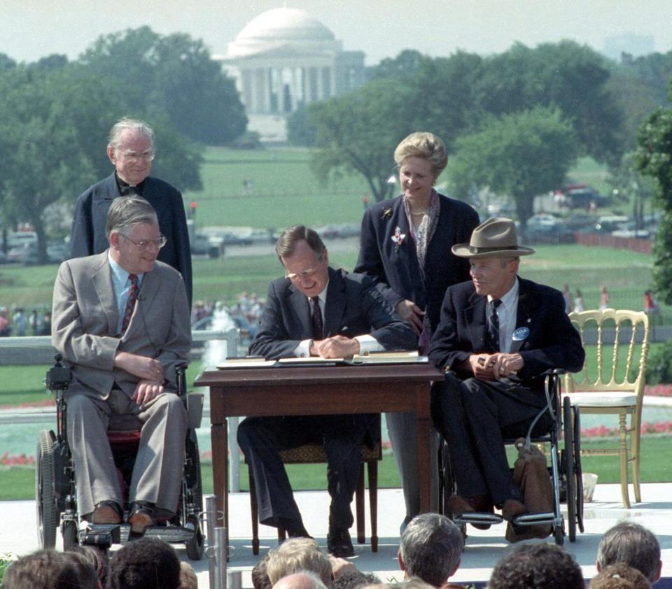 President George H.W. Bush (center) signs the Americans with Disabilities Act of 1990.