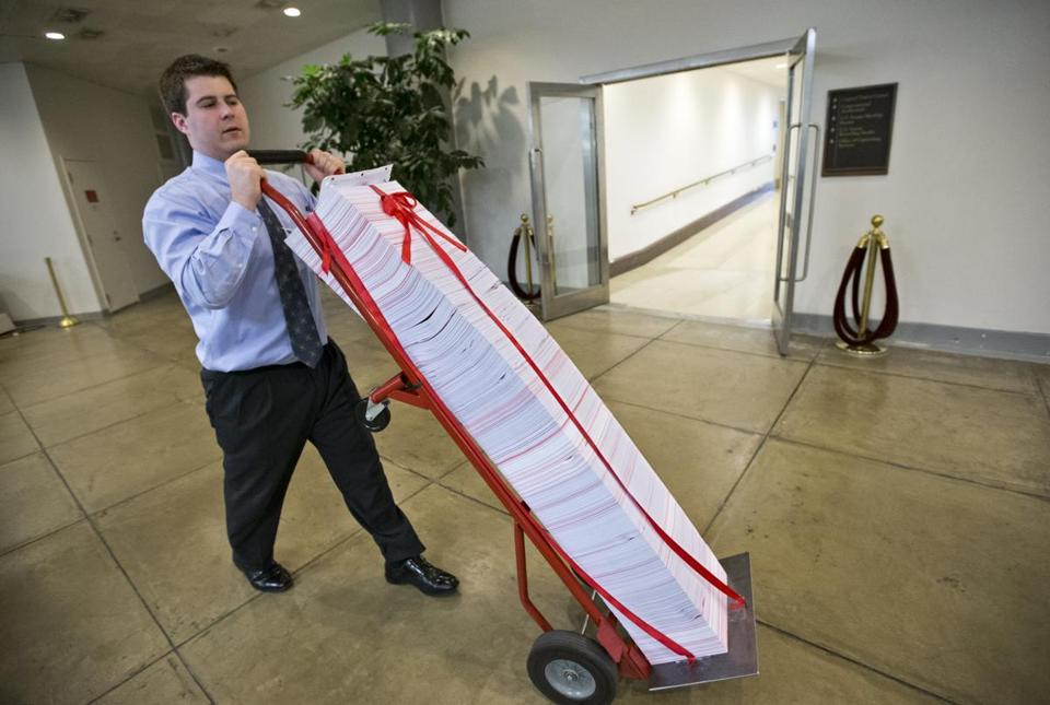 A Senate aide delivered a stack of documents in red tape being used as a prop during debate on the budget in the Senate.