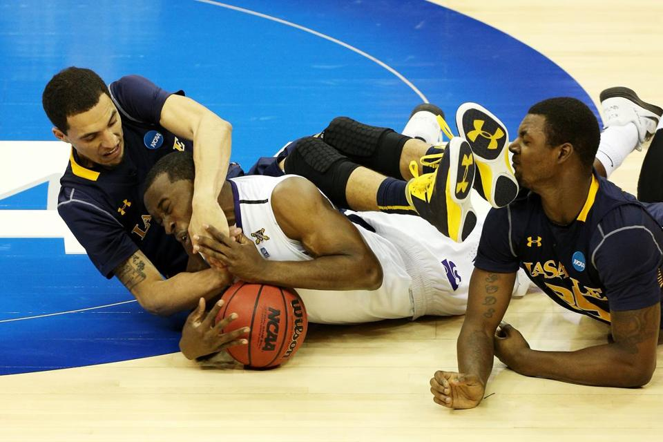 Martavious Irving of the Kansas State Wildcats fought for possession of the ball against D.J. Peterson (left) and Jerrell Wright of the La Salle Explorers.