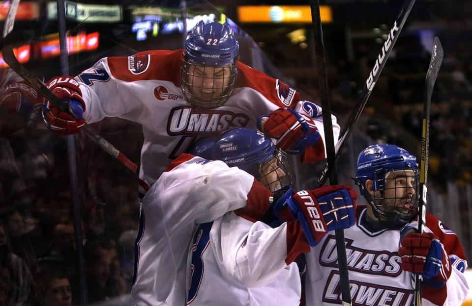 Defenseman Gregory Amlong (22) leaps into the pile after UMass-Lowell went ahead in the third period.