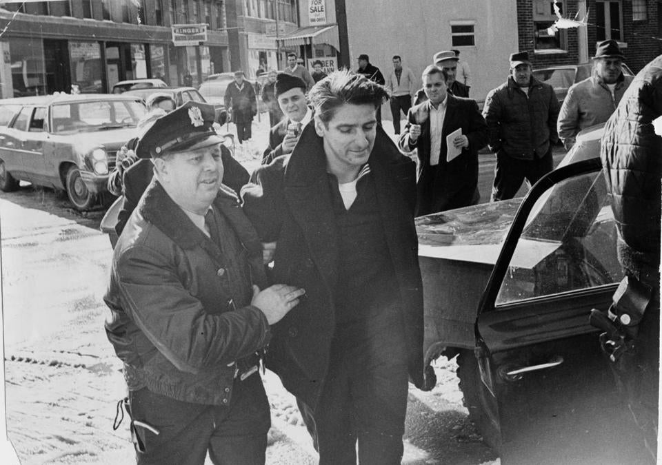 Albert DeSalvo (center) is escorted from a Lynn police station on Feb. 2, 1967. Police are now investigating if DeSalvo was telling the truth when he confessed to being the Boston Strangler.