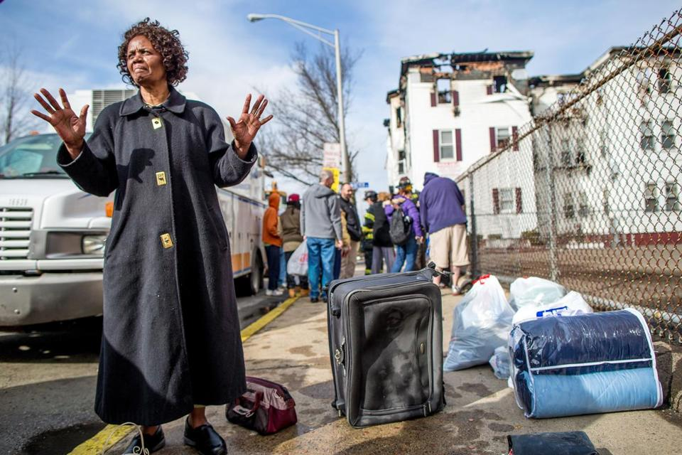 Zaina Saidi stood with her few belongings on Monday after a fire at her Lynn apartment building.
