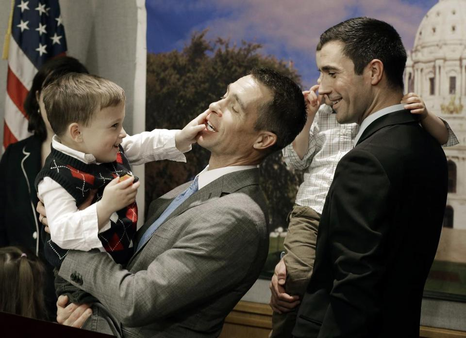 Dr. Paul Melchert, left, was interrupted by his son, Emmett, as he addressed the media while his partner James Zimerman held Emmett's twin brother, Gabriel, during a  Feb. 27 news conference in St. Paul, Minn., where lawmakers introduced a bill to legalize gay marriage in that state.