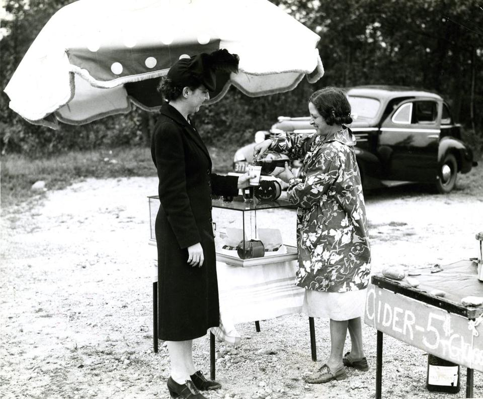 October 20, 1940: Mrs. Edwin Benson of Arlington purchases a glass of home-made cider from Miss Marion Thurston of the Paine-Elm Farm roadside stand in Concord.