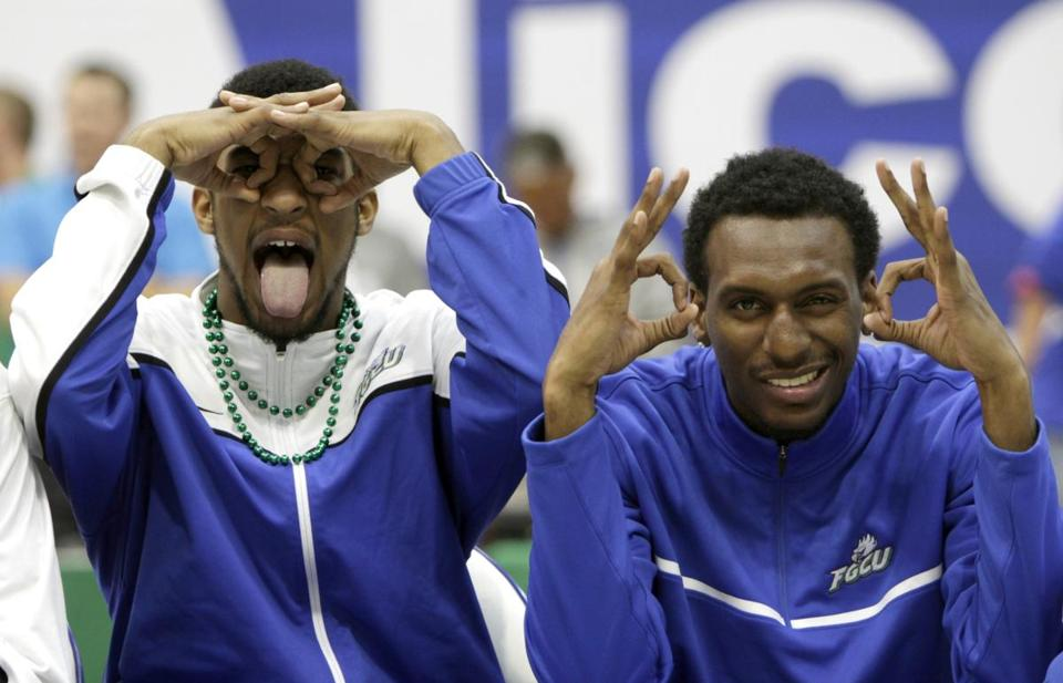 "Florida Gulf Coast's Dajuan Graf (left) and Bernard Thompson use their ""Eagle Eyes"" to view a pep rally crowd."