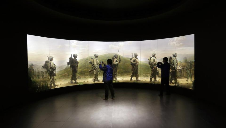 Visitors took souvenir photos this month in front of an exhibit depicting South Korean soldiers at the War Memorial of Korea in Seoul.