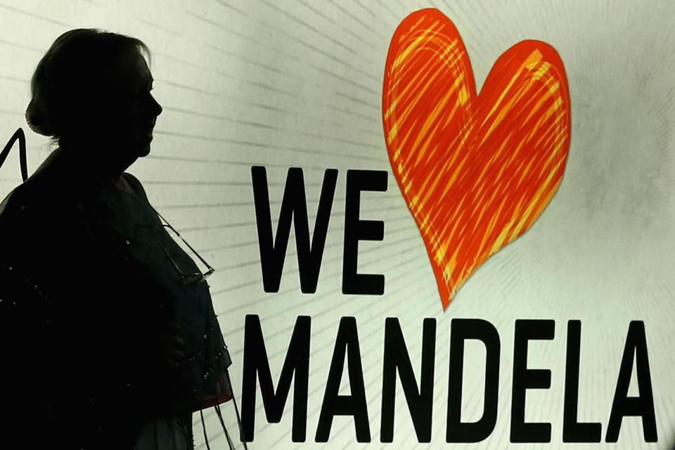 A woman walked past a lit sign supporting Nelson Mandela at his namesake shopping square in Johannesburg Monday.