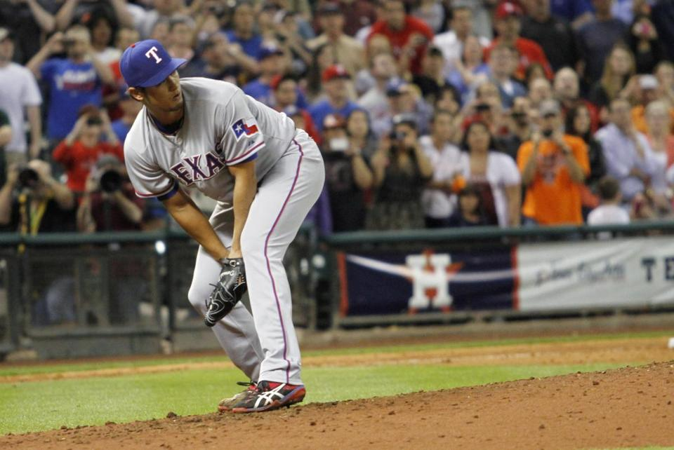 Rangers ace Yu Darvish watches after a ground ball by the Astros' Marwin Gonzalez goes into center field for a hit, spoiling his try for a perfect game.