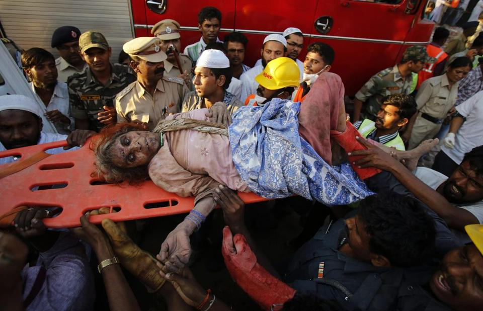 Workers removed a woman rescued a day after the collapse of a residential building outside Mumbai.