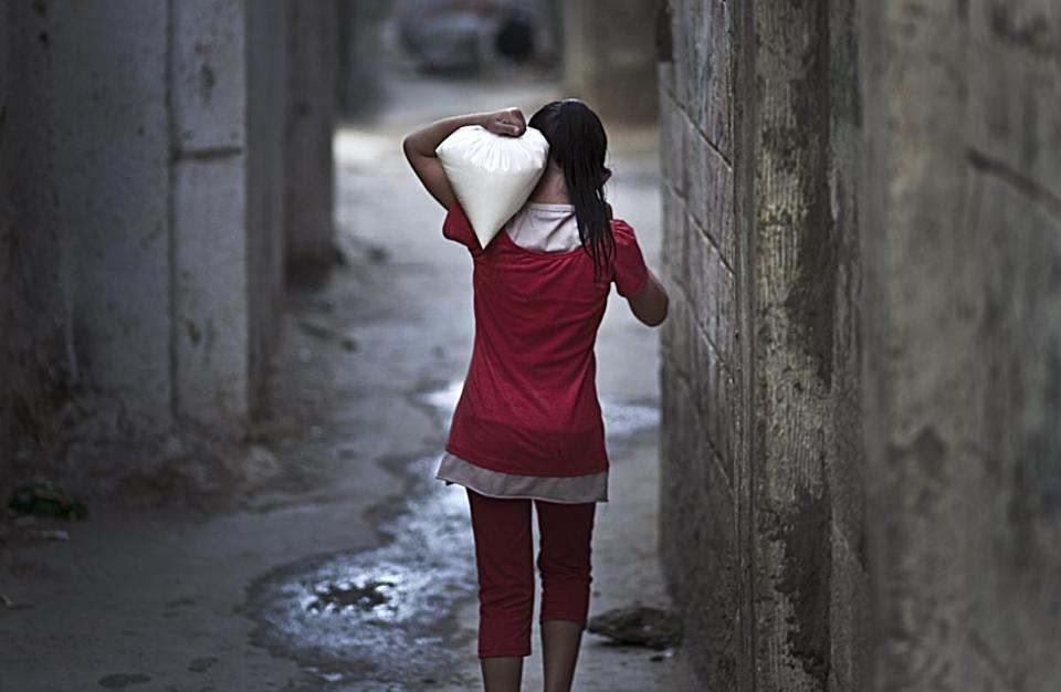 A Palestinian girl carried food supplies in a northern Gaza Strip refugee camp.