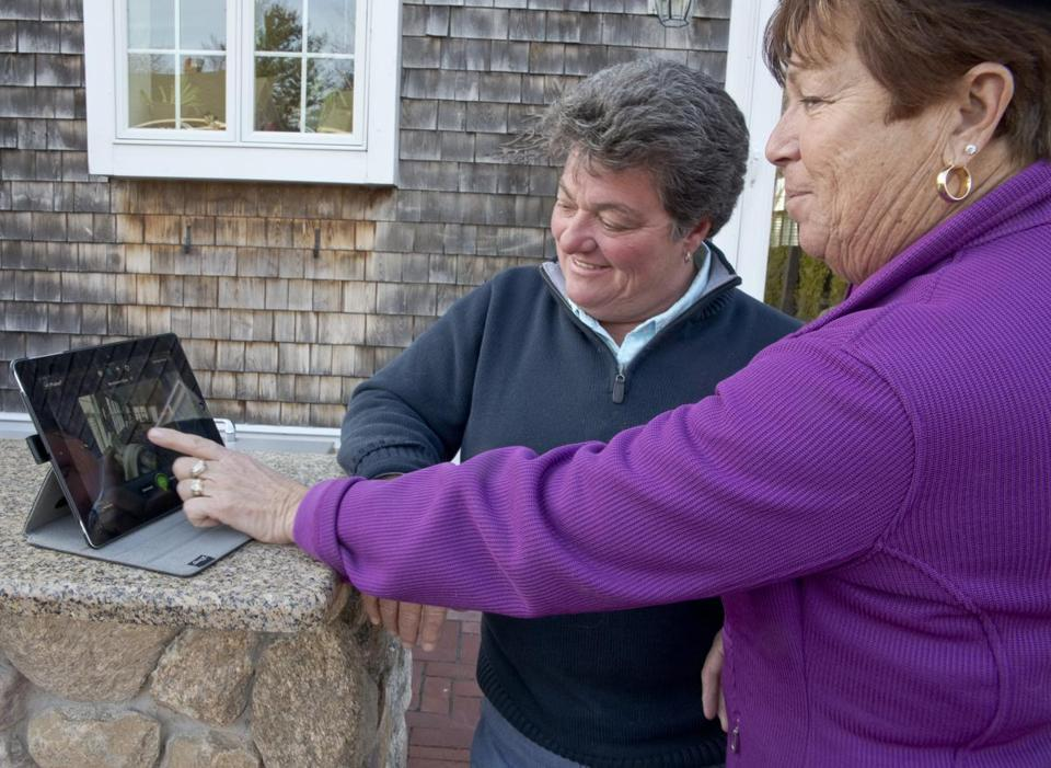 Deb Balboni (left) and her partner, Merle Balboni, use an iPad to check a security camera view.
