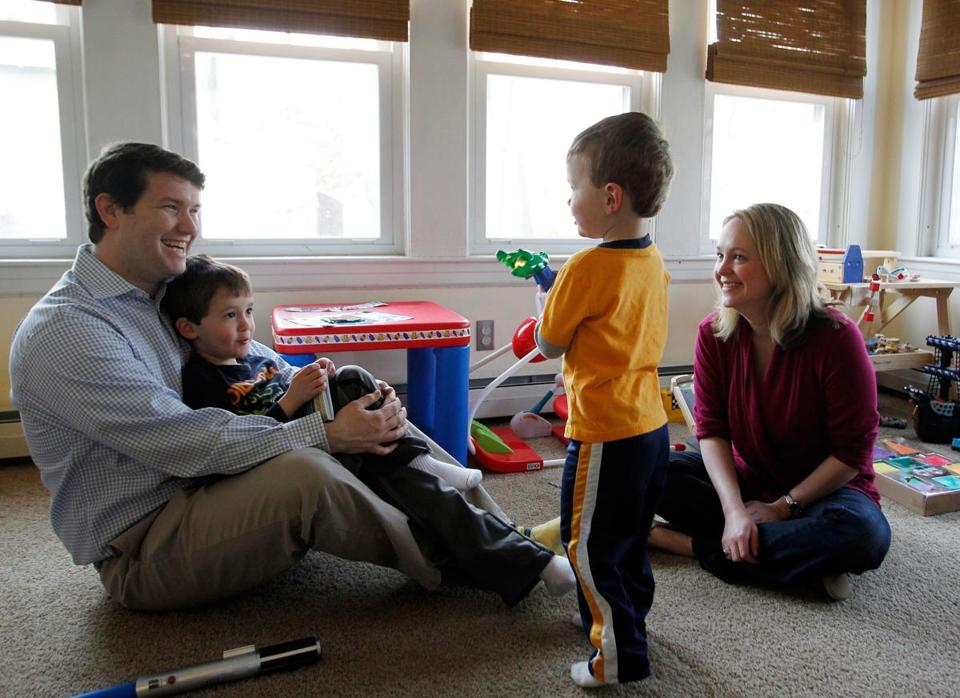 (L-R) Heath Luedde holds his son Evan, 5, as John, 2, shines a toy flashlight at them as their mother, Jessica, looks on at their home in Stoneham, Massachusetts April 7, 2013. The Luedde's are looking to relocate to Bedford because of better schools.