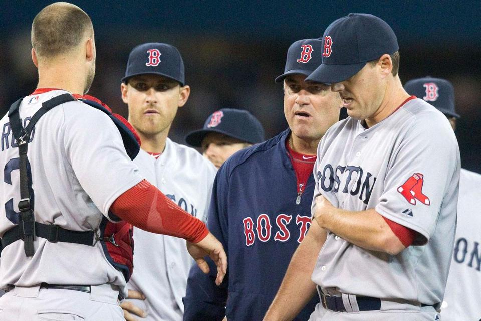 Catcher David Ross, third baseman Will Middlebrooks, and manager John Farrell surround John Lackey after he hurt his biceps in the fifth inning.
