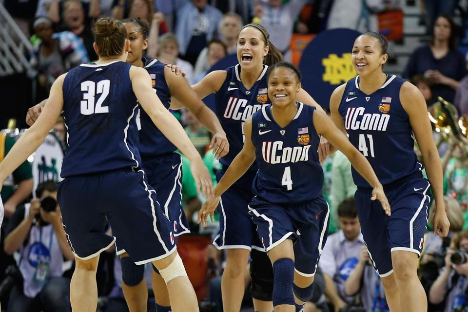 UConn players spill out onto the court, toward Heather Buck (32), after wrapping up their semifinal victory.