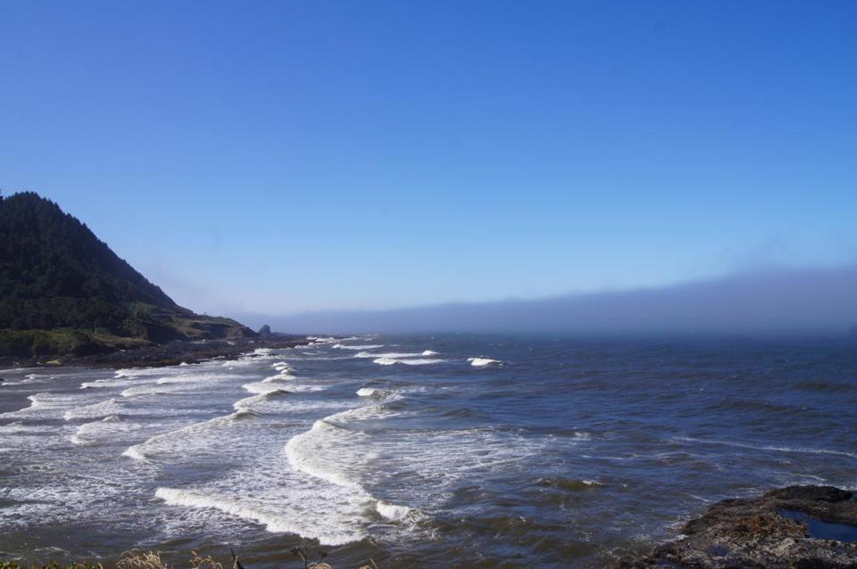 "Fog hangs in a ""marine layer"" off Cape Perpetua on midcoast Oregon, the warm air from Willamette Valley cooled by the Pacific Ocean. The moisture takes another form in the forest mist of the Cape Perpetua Scenic Area."
