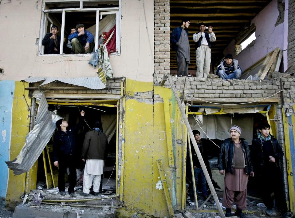 Afghans inspected destruction near the Kabul traffic police headquarters buliding, which was attacked by the Taliban in January.