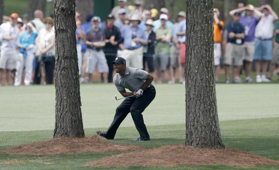 Tiger Woods bends to get a good look at his approach shot on No. 7 at Augusta National. Woods is looking for his first Green Jacket since 2005.