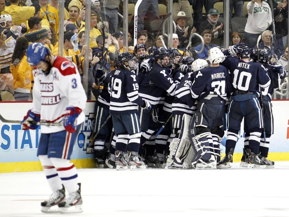 UMass-Lowell's Chad Ruhwedel skates away dejectedly as Yale players celebrate Thursday night's semifinal win in OT.