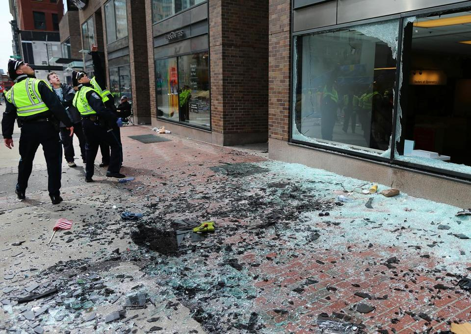 Boston Police examined blown-out windows at the scene of the first explosion on Boylston Street.