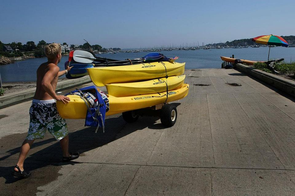 Kevin Drislane sets up rental boats at Riverhead Beach on Marblehead Harbor at the height of summer.