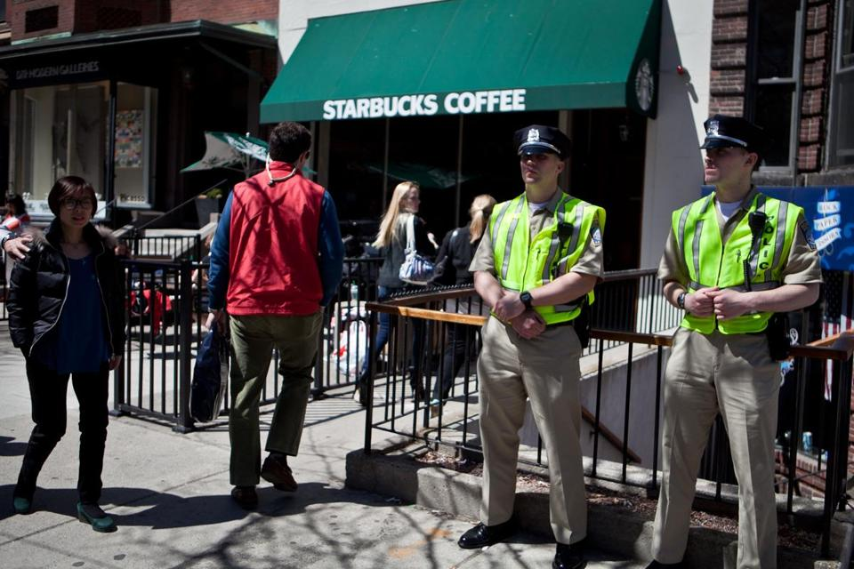 Even as officers stood guard over its patio, the Starbucks Coffee on Newbury Street reopened for business Wednesday to a heavy flow of customers.