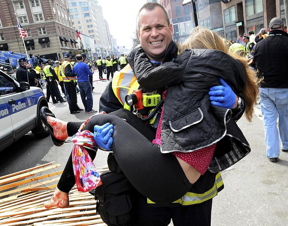 Boston Firefighter James Plourde carries an injured girl away from the scene after the Marathon bombing.