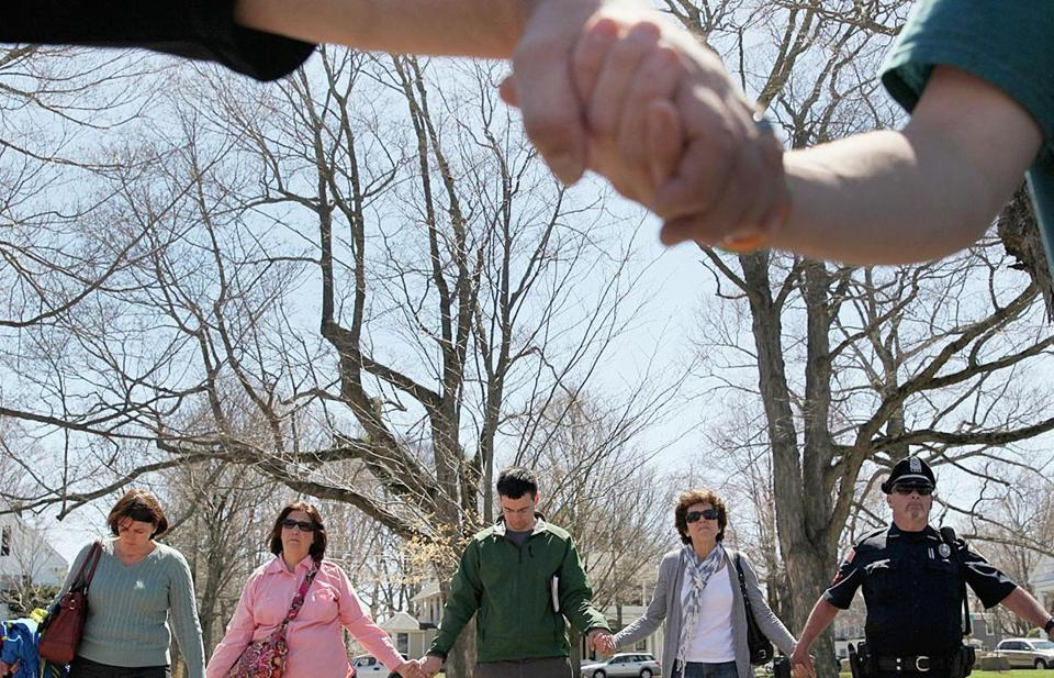 In Hopkinton, people held hands in a vigil near the Boston Marathon starting line Wednesday.