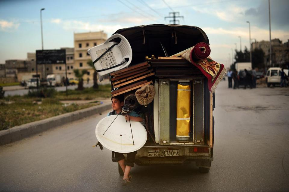 A Syrian boy held a satellite antenna as he traveled on the back of a truck in Aleppo on Monday. Some 1.3 million people have so far fled Syria since the start of the conflict.