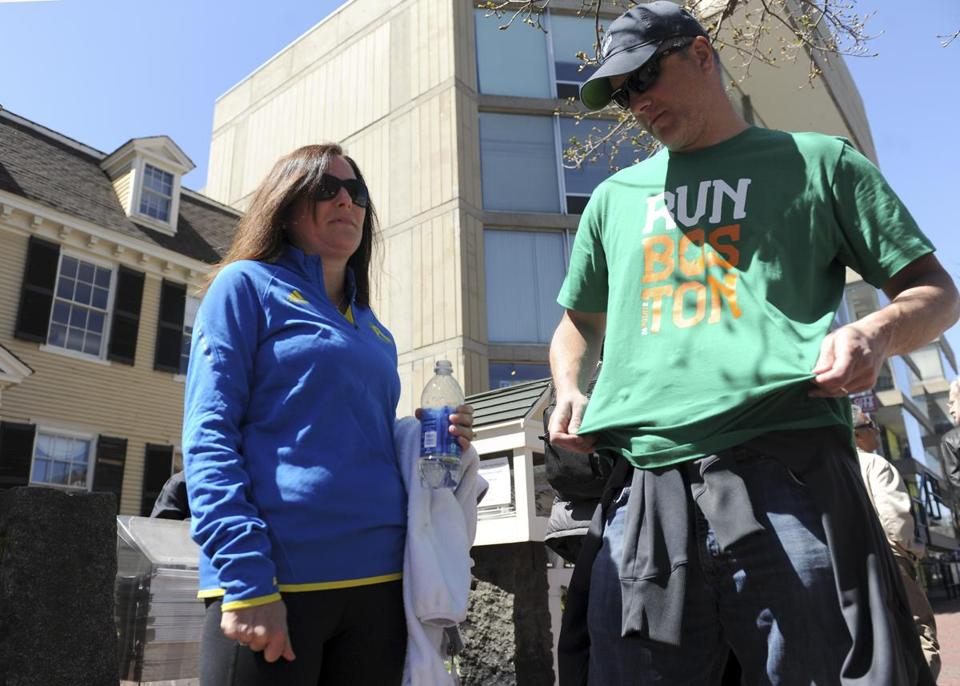 Damien King of Seattle donned a Boston Marathon T-shirt Wednesday, a move that has taken on new significance. He was in Boston to support his wife, Jennifer (left). who ran the race.